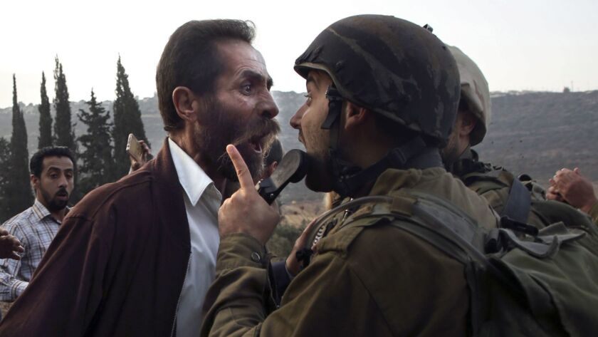 A Palestinian man argues with an Israeli soldier in the town of as-Sawiyah, south of Nablus last month in the occupied West Bank. This week Israeli Prime Minister Benjamin Netanyahu disputed the idea that the West Bank, administered by the Israeli army, is occupied territory.