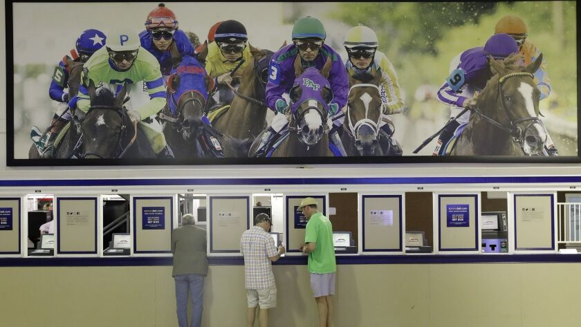 FILE - In this May 19, 2017 file photo, fans place bets ahead of the running of the Black-Eyed Susan