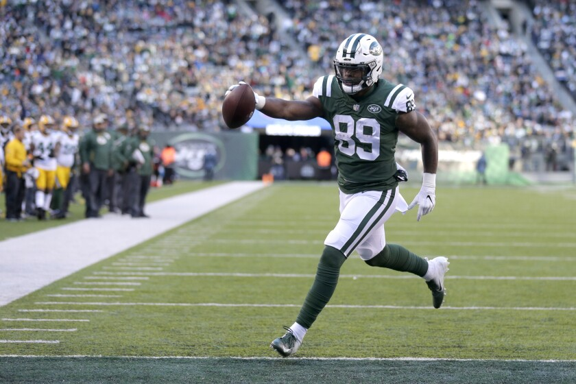 FILE - In this Dec. 23, 2018, file photo, New York Jets tight end Chris Herndon scores on a touchdown pass from quarterback Sam Darnold during the second half of an NFL football game against the Green Bay Packers in East Rutherford, N.J. Herndon was all set for a big breakout season a year ago with the Jets. A four-game suspension and a few tough injuries put those plans on hold. Now, the third-year tight end is ready to make up for lost time. (AP Photo/Seth Wenig, File)