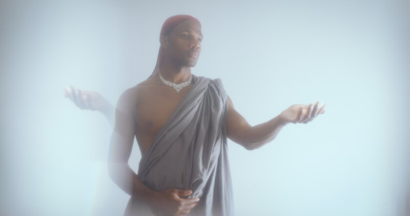 """Wearing a diamond necklace and red durag, Derrell Acon performs """"Songs to the Dark Virgin."""""""
