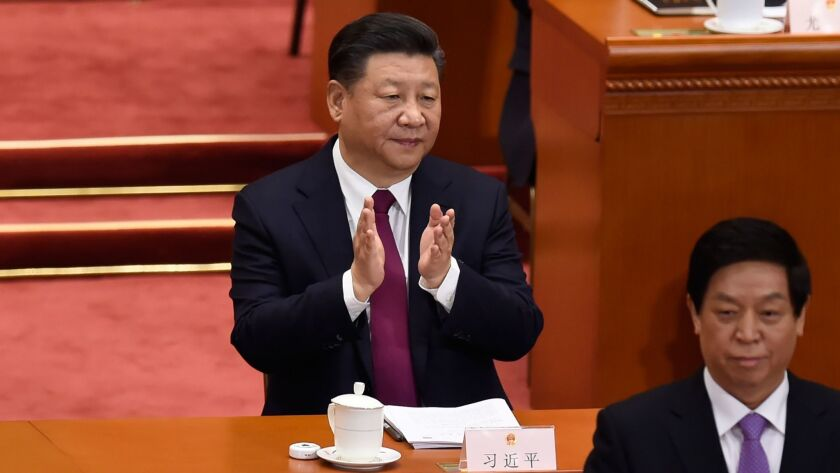 Chinese President Xi Jinping applauds during the opening session of the National People's Congress, China's legislature, at the Great Hall of the People in Beijing on March 5, 2018.