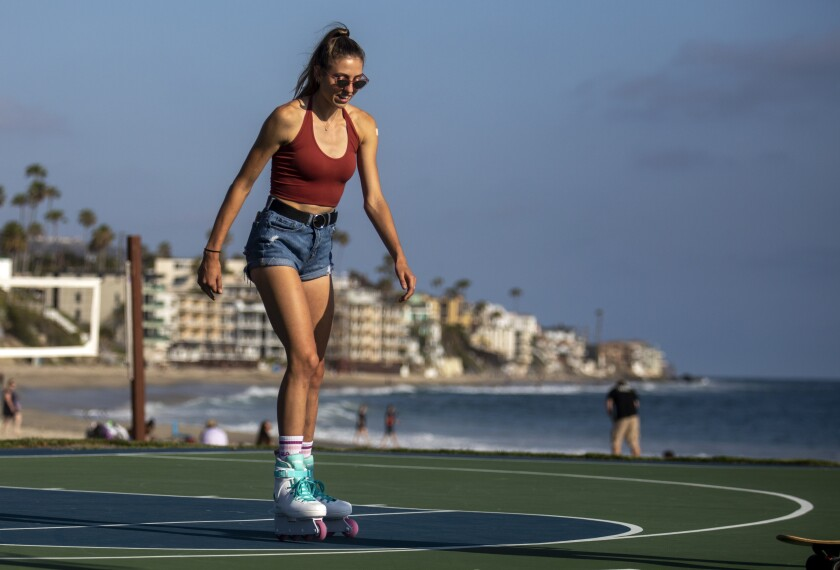 Catherine Dahlberg, 18, of Fullerton celebrates getting her second vaccination by skating in Laguna Beach.