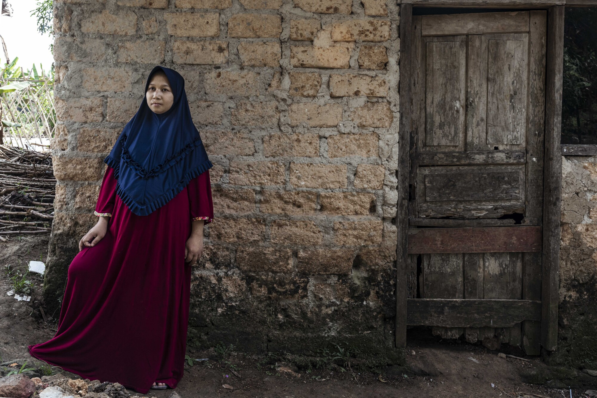 A woman in a red robe and blue hijab stands in front of a brick wall near a wooden door