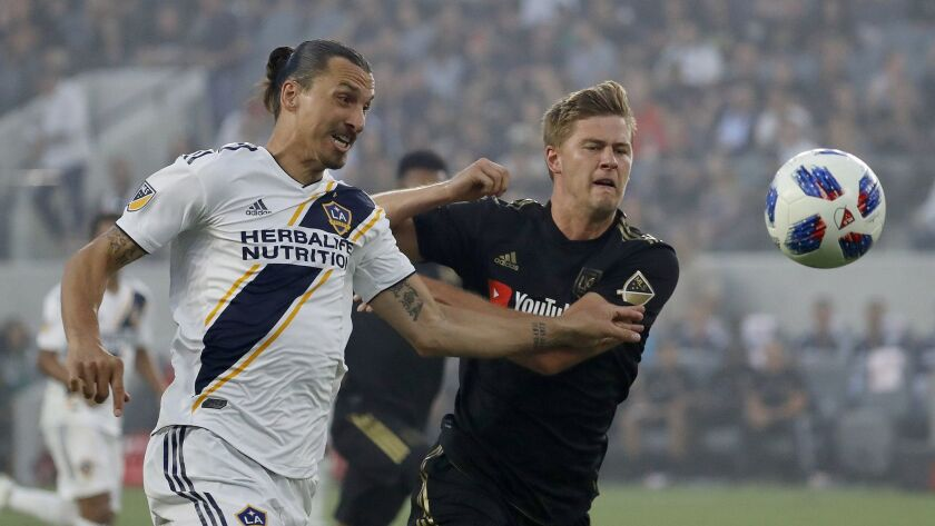 LAFC defender Walker Zimmerman, right, battles Galaxy forward Zlatan Ibrahimovic for control of the ball in the first half at the Banc of California Stadium on July 26.
