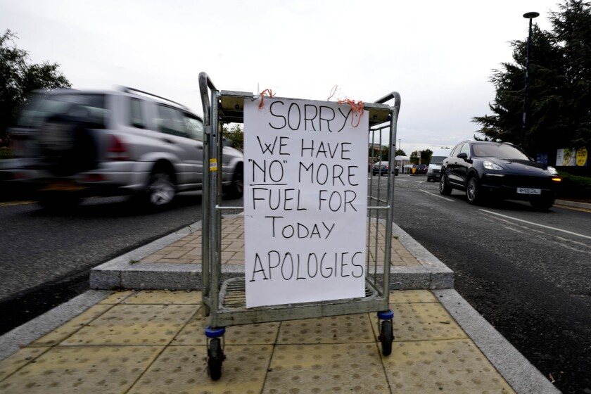 A sign referring to the lack of fuel is placed at the entrance to a petrol station in London, Tuesday, Sept. 28, 2021. Long lines of vehicles have formed at many gas stations around Britain since Friday, causing spillover traffic jams on busy roads. (AP Photo/Frank Augstein)