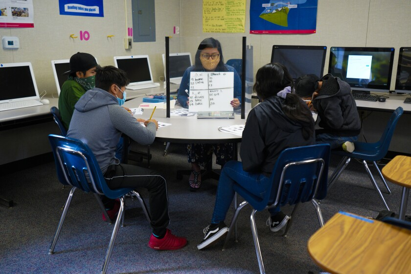 Selena Hernandez, a bilingual instructional aide at Oak Crest Middle School in Encinitas, works with her students.