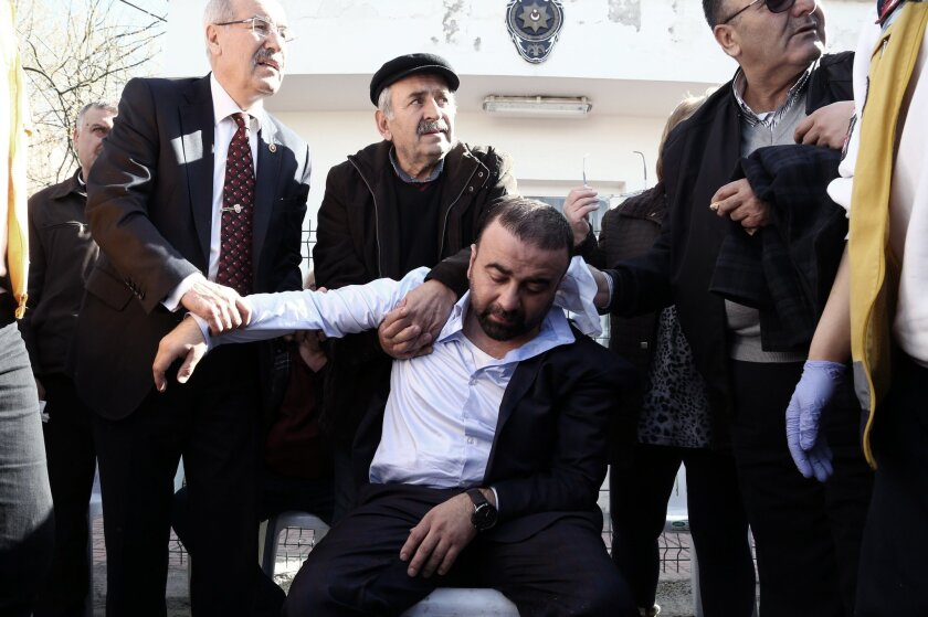 Medics and people help a collapsed relative of a victim outside the medical forensics site in Ankara, Turkey, Thursday, Feb. 18, 2016. A Syrian national with links to Syrian Kurdish militia carried out the suicide bombing in Ankara that targeted military personnel and killed at least 28 people, Tur