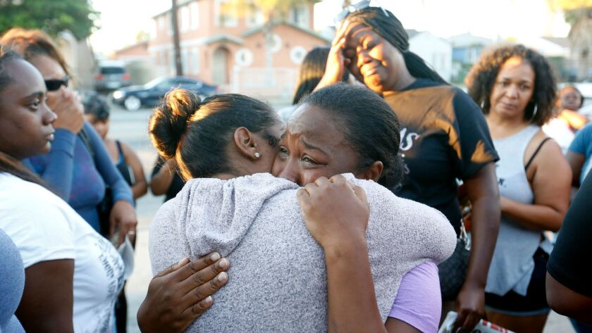 Prescious Sasser cries as she hugs a friend at a vigil for her 18-year-old son, Kenney Watkins, afte