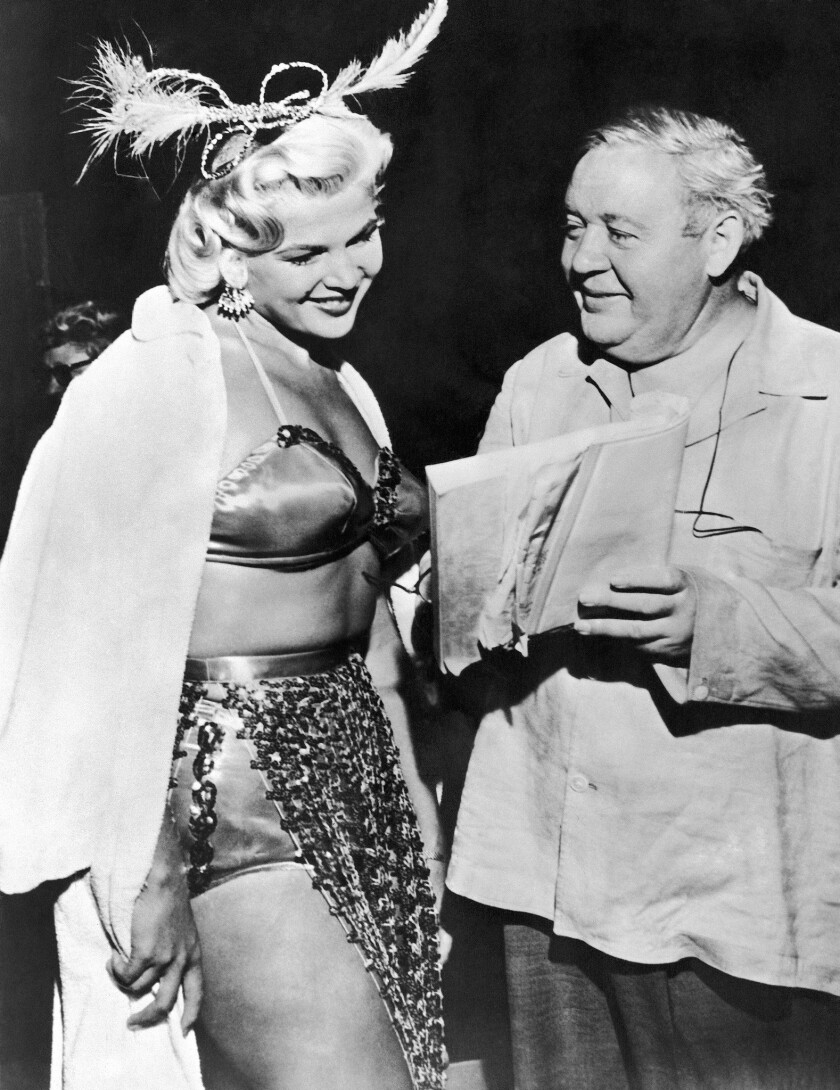 """English-American veteran actor Charles Laughton, launching a new career as a movie director, goes over the script with dancer Gloria Pall on the set of """"The Night of the Hunter."""" Gloria plays a burlesque queen in the film."""