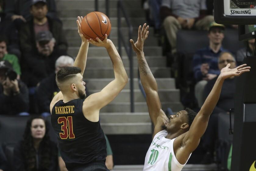 USC's Nick Rakocevic, left, shoots over Oregon's Shakur Juiston during the first half on Thursday in Eugene, Ore.