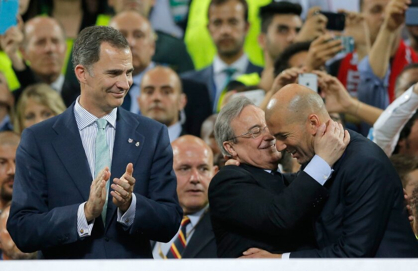 Real Madrid's headcoach Zinedine Zidane, right, is embraced by Real president Florentino Perez as Spain's King Felipe looks on during the Champions League final soccer match between Real Madrid and Atletico Madrid at the San Siro stadium in Milan, Italy, Saturday, May 28, 2016.  (AP Photo/Manu Fern