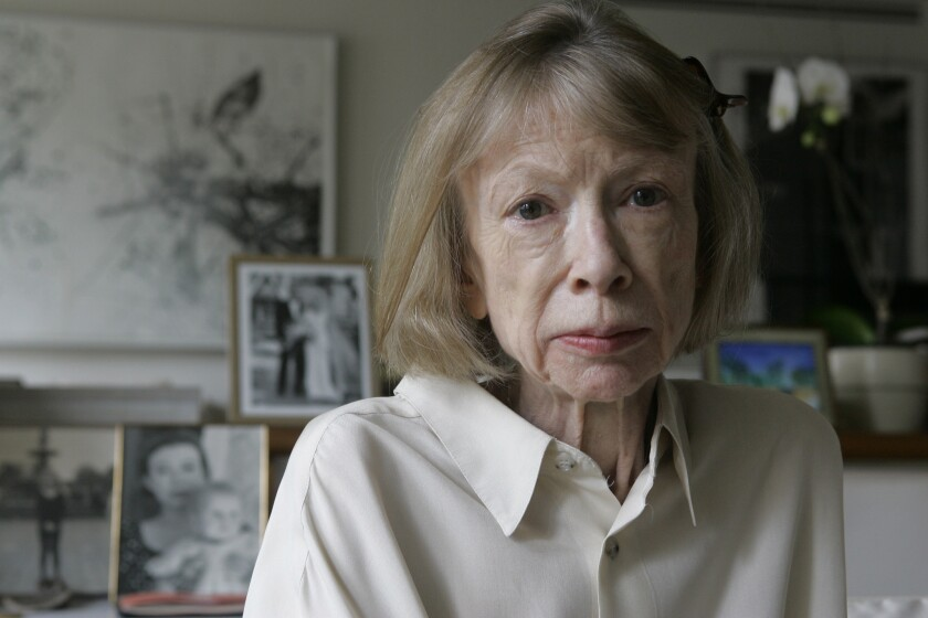 Joan Didion sits in front of a photo of herself holding her daughter, Quintana Roo, and another picture of her daughter's wedding, in her New York apartment on Sept. 26, 2005.