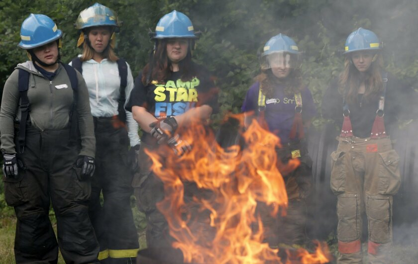 In this Monday, July 11, 2016 photo, firefighting camp participants watch as a propane fire burns during a drill in the use of fire extinguishers at a fire station in Ashland, Mass. Camp Bailout is one of about a dozen all-girl firefighting camps around the nation, seen as crucial in boosting the n