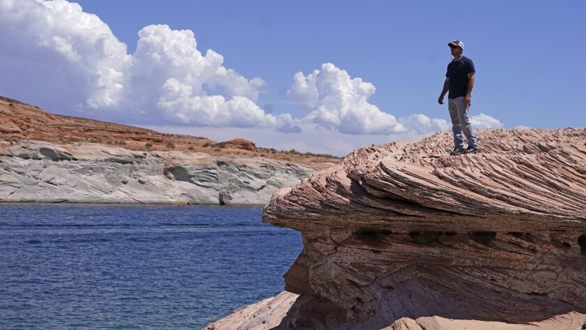 Bill Schneider stands near Antelope Point's public launch ramp off Lake Powell, which closed to houseboats as early as October of 2020 Saturday, July 31, 2021, near Page, Arizona. This summer, the water levels hit a historic low amid a climate change-fueled megadrought engulfing the U.S. West. (AP Photo/Rick Bowmer)