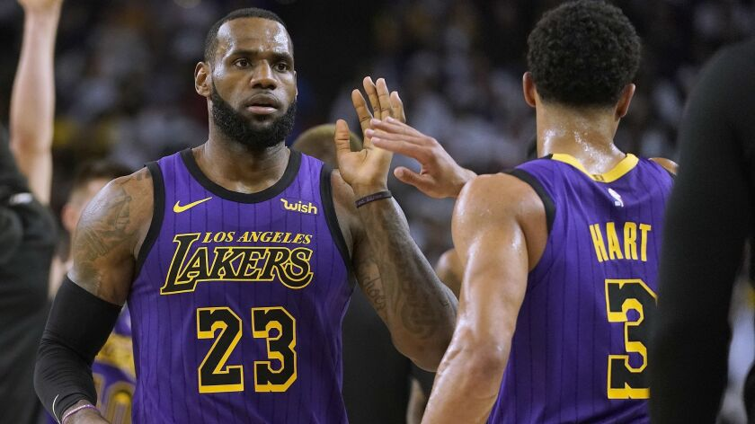 Lakers forward LeBron James high-fives Josh Hart at the end of the first half against the Golden State Warriors on Tuesday in Oakland.
