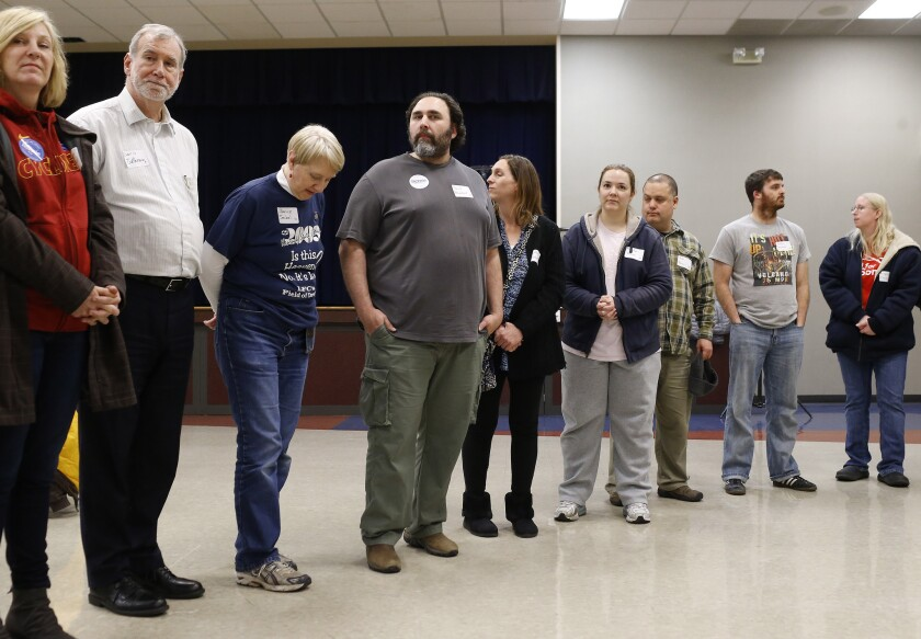Supporters of candidate Bernie Sanders stand in line while they are counted during a Democratic Party caucus in Nevada, Iowa, on Monday.