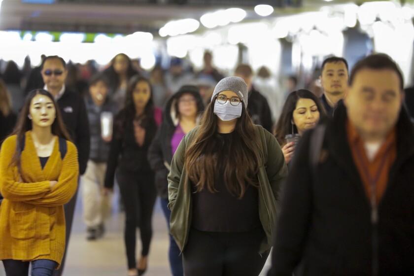 Travelers wearing sanitary masks amid worries about the spread of coronavirus. (Irfan Khan / Los Angeles Times)