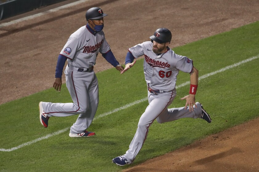 Minnesota Twins' Jake Cave (60) runs to score on a single hit by Eddie Rosario against the Chicago Cubs during the sixth inning of a baseball game, Saturday, Sept. 19, 2020, in Chicago. (AP Photo/Kamil Krzaczynski)