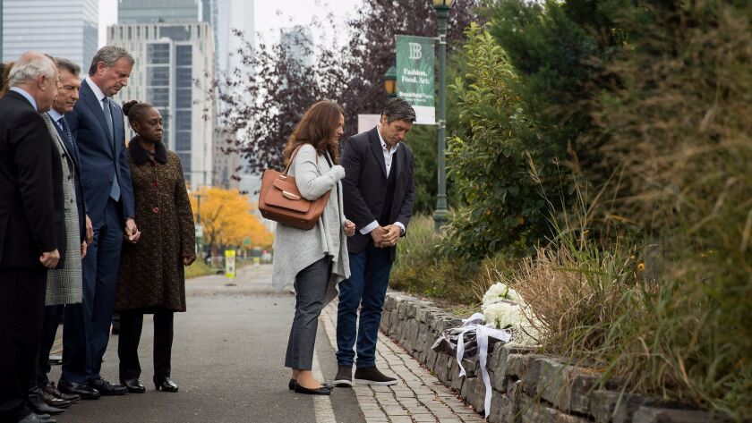 ArgentinePresident Mauricio Macri, New York City Mayor Bill de Blasio and Chirlane McCray look as attack survivor Guillermo Banchini and a fellow mourner pause during a tribute for the victims of last week's bike path attack.