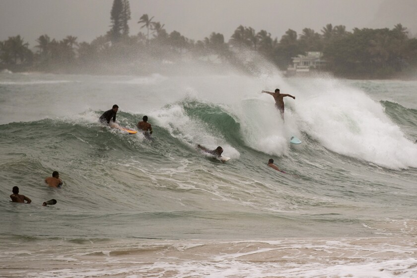 Surfers take on large waves generated by Hurricane Douglas on Sunday at Laie Beach Park on Oahu.