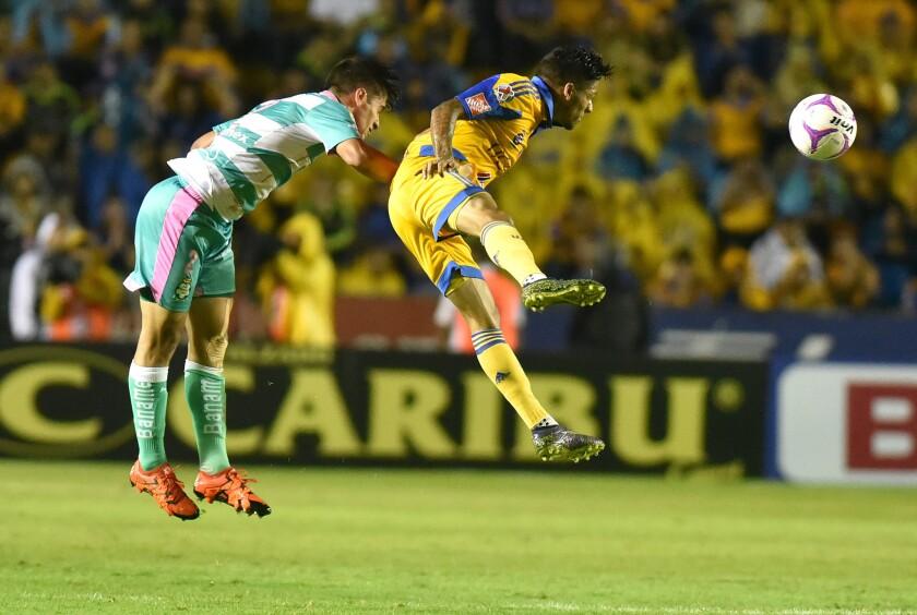 Javier Aquino (d) Tigres disputa el balón contra José Abella (i) del Santos, en el estadio Universitario de Monterrey, México.