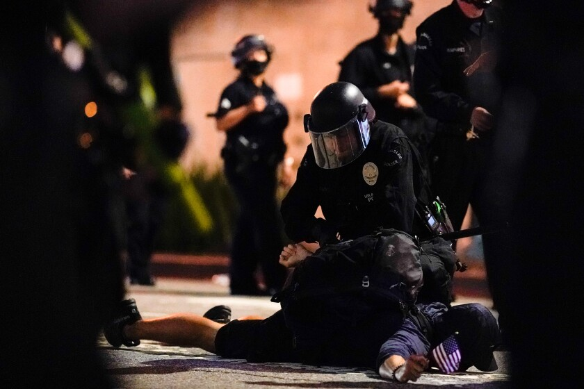 A protester is detained in Los Angeles in late May.