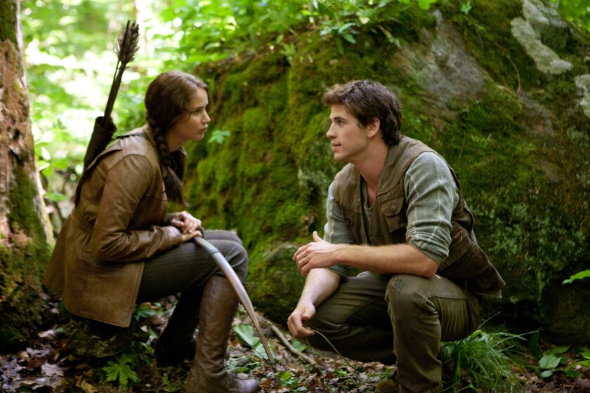 """Jennifer Lawrence as Katniss Everdeen and Liam Hemsworth as Gale Hawthorne in the movie """"The Hunger Games,"""" which was filmed in North Carolina."""