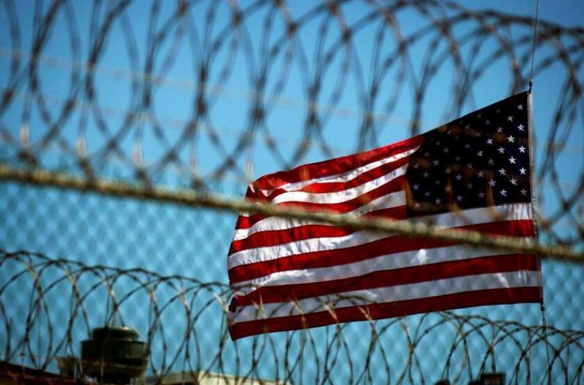 Fotografía que muestra una bandera estadounidense junto a un alambrado en un perímetro de seguridad de un cárcel. EFE/Archivo