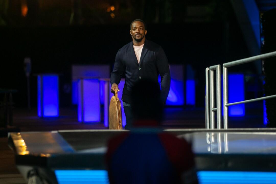 Anthony Mackie walks on stage in a dark jacket.