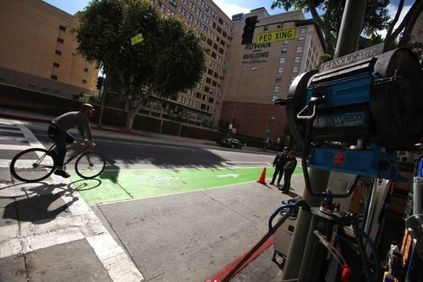 """Cyclist in green bike lane on Spring Street in downtown L.A. passes film crew working on the show """"Ringer"""" last year."""