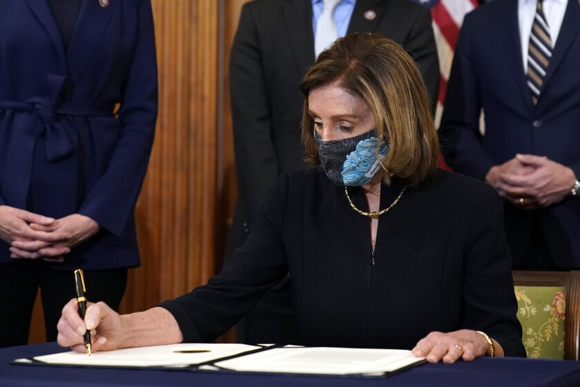 Nancy Pelosi, seated with pen in hand, signs a document.