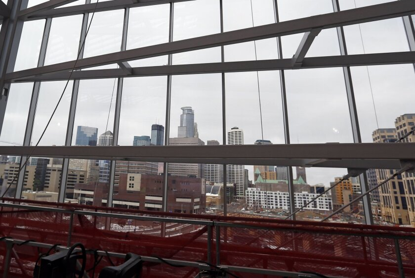 The Minnepaois skyline is visible through one of five glass pivoting doors during a media tour, Tuesday, Feb. 16, 2016, of the new US Bank stadium in Minneapolis which will be home to the Minnesota Vikings NFL football team.  (AP Photo/Jim Mone)