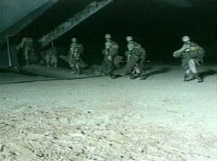 """FILE - This file image from video released by the U.S. Defense Department and made available Oct. 20, 2001, shows U.S. special forces boarding an unidentified aircraft at an unknown location, the day Joint Chiefs of Staff Chairman, Gen. Richard Myers, announced at the Pentagon that U.S. special forces """"attacked and destroyed targets"""" in Afghanistan. The Central Intelligence Agency together with U.S. special operations were the first Americans into Afghanistan after the attacks of Sept. 11th, and will likely be the last U.S. forces to leave. (AP Photo/DOD Pool, File)"""