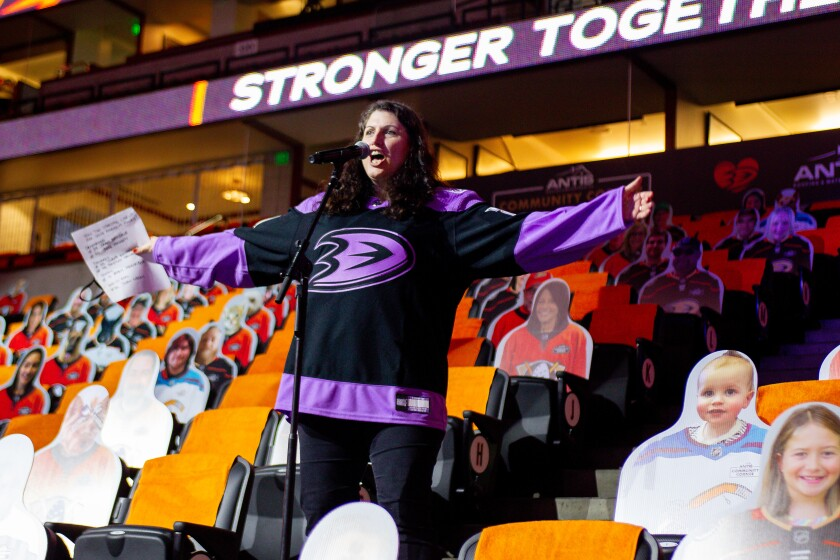 Arms wide open, Angelique Fong stands at a microphone and introduces the Ducks before their game April 11 at Honda Center.
