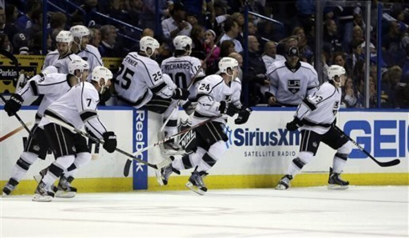 Members of the Los Angeles Kings rush off the bench to congratulate teammate Slava Voynov, of Russia, on his game-winning goal during overtime in Game 5 of a first-round NHL hockey Stanley Cup playoff series against the St. Louis Blues Wednesday, May 8, 2013, in St. Louis. The Kings won 3-2. (AP Photo/Jeff Roberson)