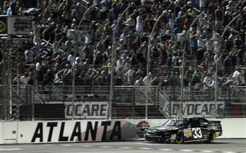 Driver Kevin Harvick (33) crosses the finish line to win the Nationwide Series auto race at Atlanta Motor Speedway, Saturday, Aug. 31, 2013, in Hampton, Ga. (AP Photo/David Tulis)
