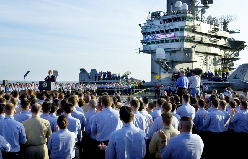 A crowd faces George W. Bush, who stands at a podium on an aircraft carrier.