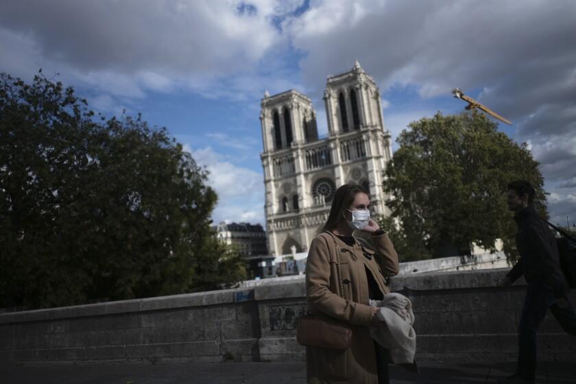 Una mujer camina frente a la catedral de Notre Dame el sábado 26 de septiembre de 2020 en París, Francia. (AP Foto/Lewis Joly)