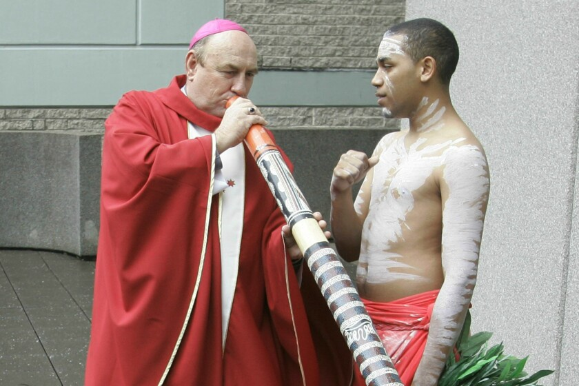Bishop Christopher Alan Saunders tries to play a digeridoo while another man stands next to him.