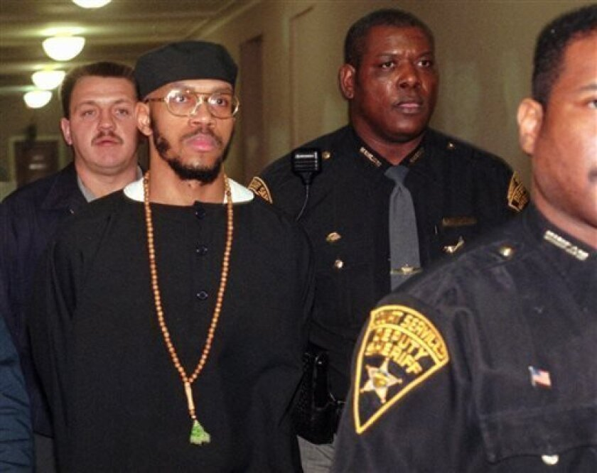 FILE - This Tuesday, Jan. 16, 1996 file photo shows Carlos Sanders, with cap, under heavy guard as he is led to court in Cincinnati, where jury selection began on his aggravated murder, kidnapping, and assault trial. Sanders is the alleged ringleader in the 1993 Lucasville prison riot. In the 20 years since the nation's longest deadly prison riot broke out in Lucasville, no interviews have been granted with the five men sentenced to death in the killing of a guard. Yet time has brought new evide