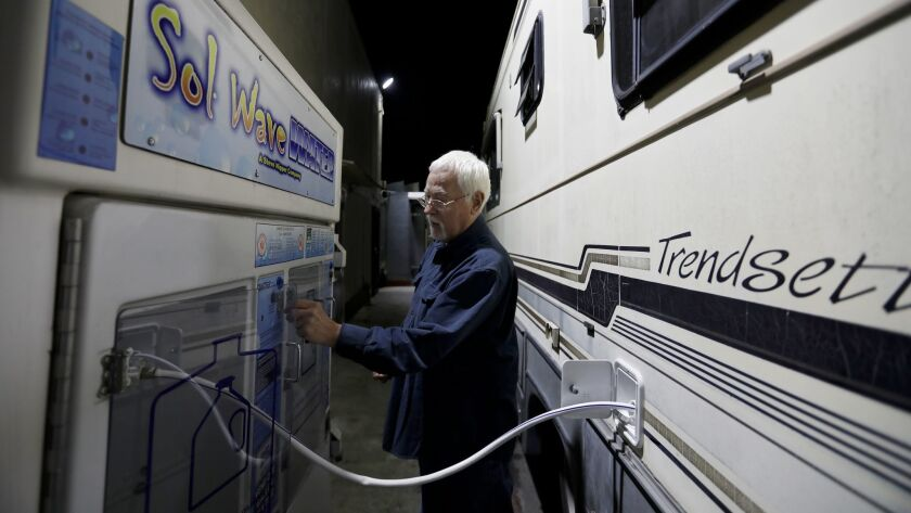 It's nearly midnight and Phil, 74, is outside his RV paying for filtered water with quarters from the vehicle.
