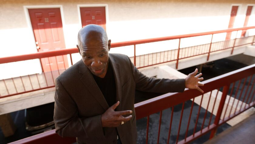 The Rev. Richard Reed, executive director of the nonprofit First to Serve€, shows visitors around a former motel that is being used to house homeless women.