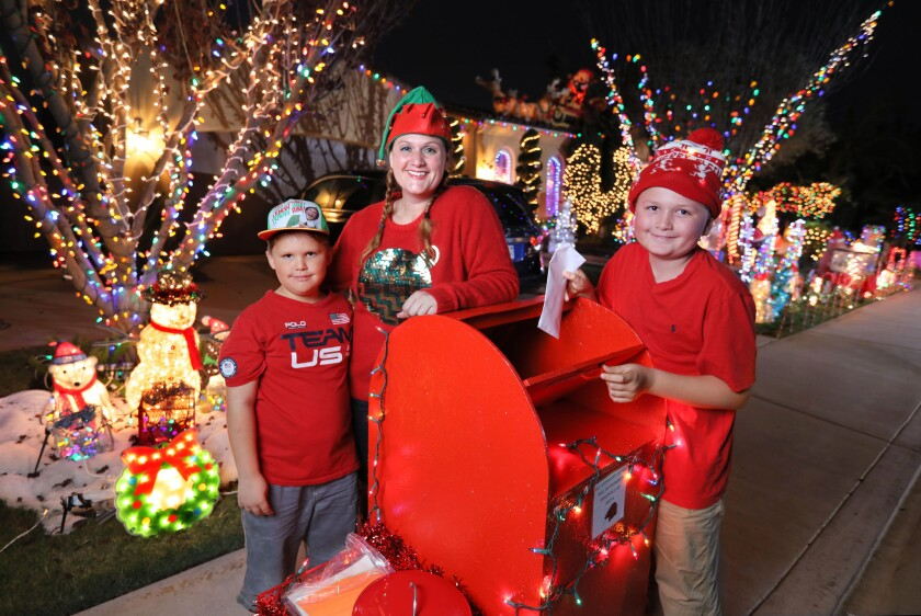 "Elizabeth Bruckner stands with her kids A.J., at left, and Wolfie, at right, at their ""Letters to Santa"" mailbox in front of their Carlsbad house in 2016."