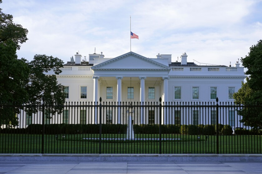 An American flag flies at half-staff over the White House on Saturday.