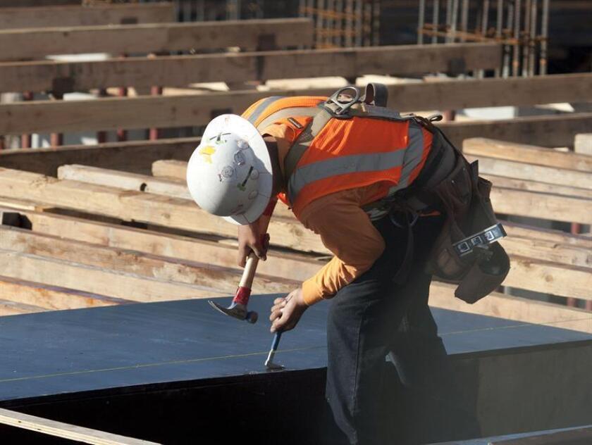 Un albañil trabaja en un edificio de apartamentos en el centro de la ciudad de Los Angeles (California). EFE/Archivo