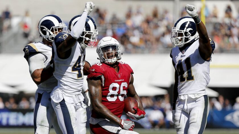 Rams defensive backs John Johnson (43) and Marqui Christian (41) celebrate after stopping Arizona Cardinals tight end Ricky Seals-Jones (86) short of the first down in the second half at the Coliseum on Sept. 16, 2018. Rams won 34-0.