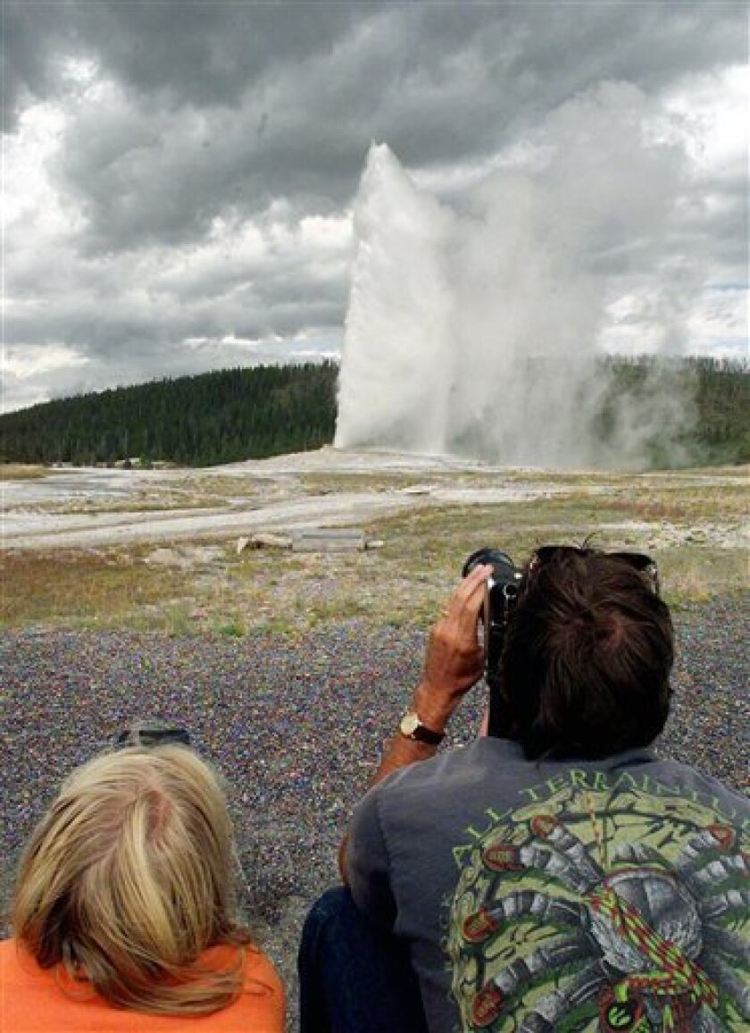 In this Friday, Aug. 15, 1997 file photo, an unidentified pair of visitors to the Yellowstone National Park photograph the Old Faithful geyser as it rockets 100-feet skyward , in Wyoming. Hundreds of small earthquakes at Yellowstone National Park in recent weeks have been an unsettling reminder fo