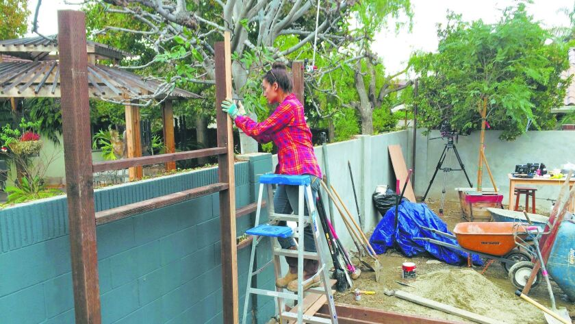 """Bendrick works on a panel wall at a client's home that was featured in """"Build It Like Bendrick,"""" a T"""