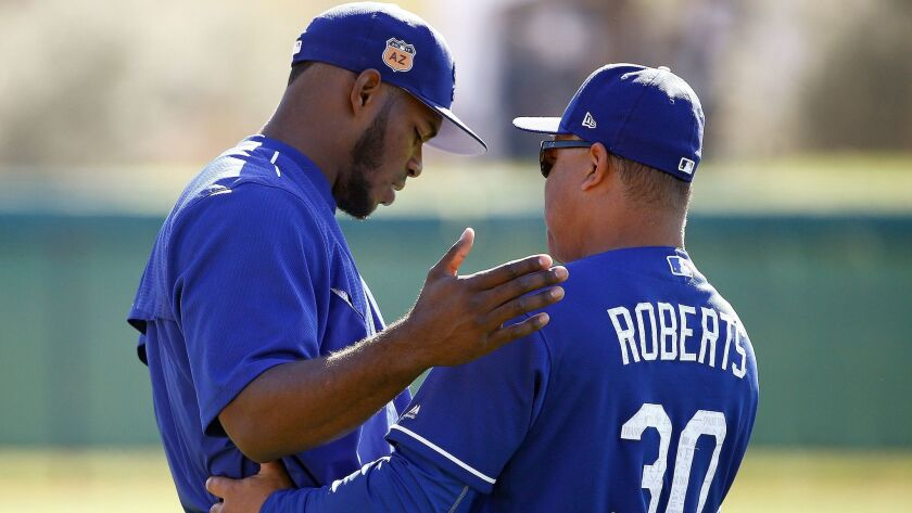 Dodgers manager Dave Roberts (30) talks with Yasiel Puig, left, at the team's baseball spring training facility Tuesday, Feb. 21, 2017, in Glendale, Ariz.