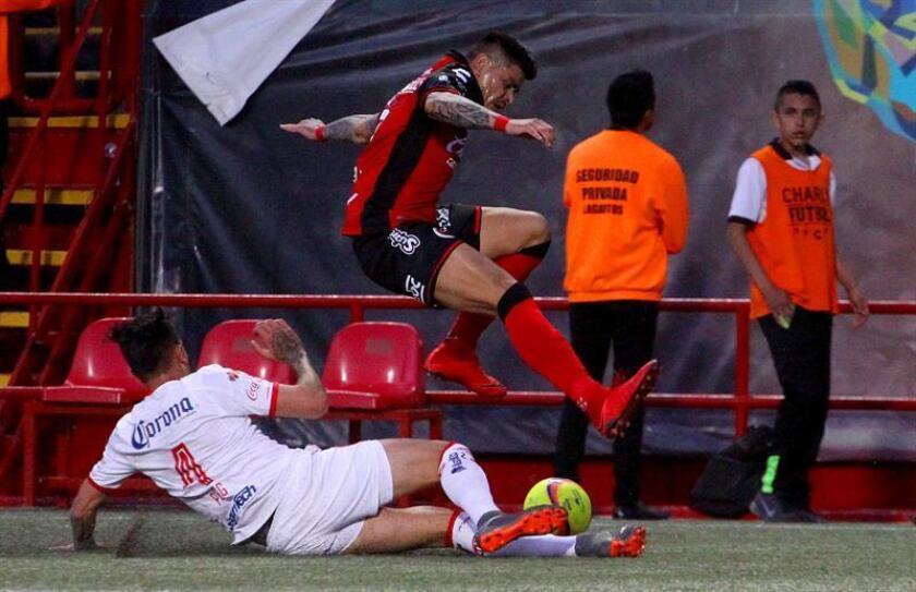 El jugador de Xolos Gustavo Bou (arriba), pelea por el balón con Maximiliano Perg (abajo) de Toluca hoy, viernes 27 de abril de 2018, durante el juego correspondiente a la jornada 17 del torneo mexicano de fútbol celebrado en el estadio Caliente en la ciudad de Tijuana (México). EFE